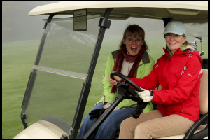 Laughing women in golfcart
